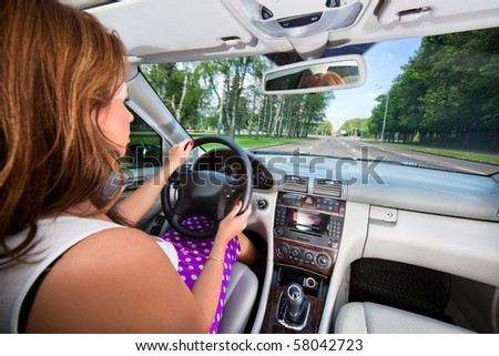 Young woman driving car. Wide angle interior view. - stock photo