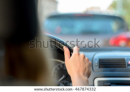 Young woman driving in traffic viewed from behind over hear shoulder with focus to her hand on the steering wheel