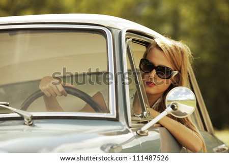 Young woman driving vintage car. - stock photo