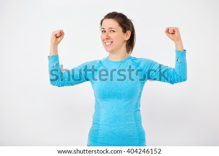 Young woman during some fitness, blue top shoot over white wall - stock photo
