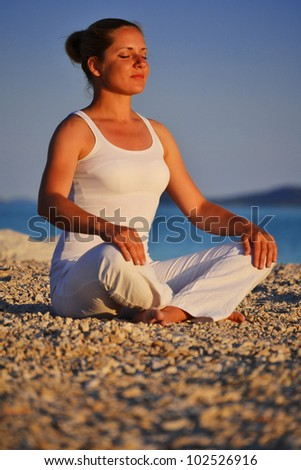 Young woman during yoga meditation on the beach - stock photo