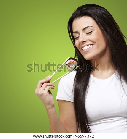 young woman eating a sushi piece against a green background - stock photo