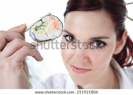 young woman eating a sushi piece against a white background - stock photo