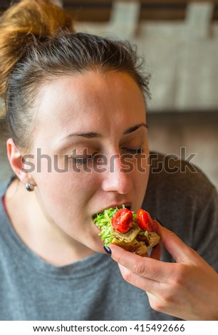 Young woman eating a vegetarian sandwich . Bread, tomatoes , artichokes and vegetables in the hands of a girl close-up .