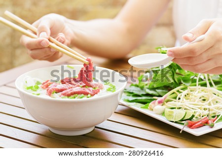 Young woman eating and enjoying the Pho Bo in street cafe of Vietnam. The Pho Bo is a traditional Vietnamese beef noodle soup with garnish of leaves of cilantro and Asian basil. Popular street food. - stock photo