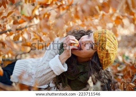 young woman eating apple outdoor in autumn - stock photo