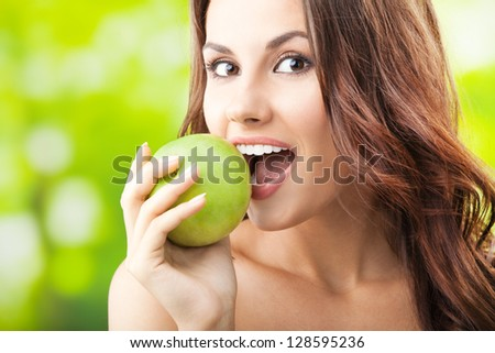Young woman eating apple, outdoors - stock photo