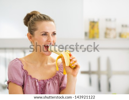 Young woman eating banana in kitchen - stock photo
