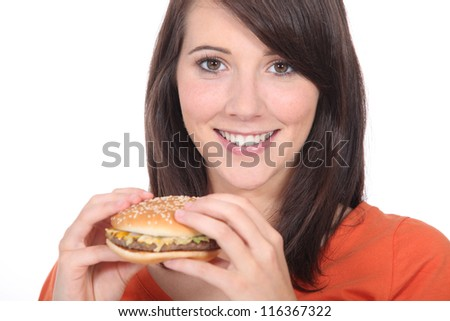 Young woman eating burger - stock photo