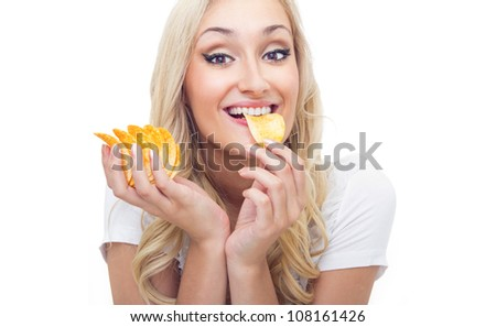 Young woman eating chips, studio-shot - stock photo