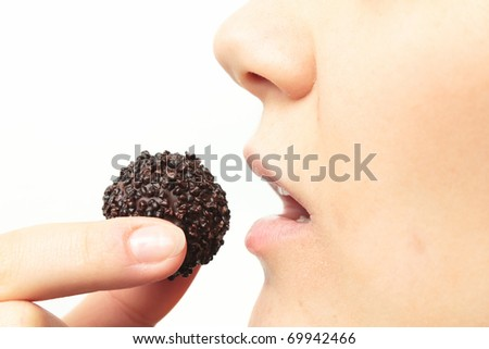 Young woman eating chocolate cookie