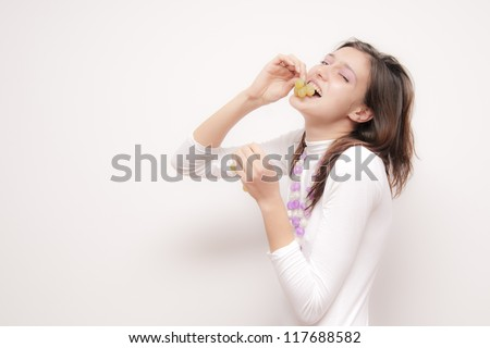 Young Woman eating grapes - stock photo
