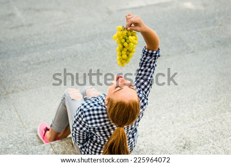 Young woman eating grapes outdoor sitting on stairs - above view - stock photo