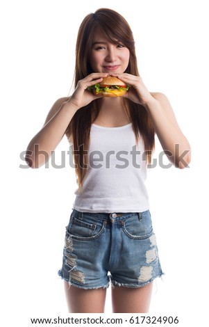 Young woman eating hamburger, isolated on white background