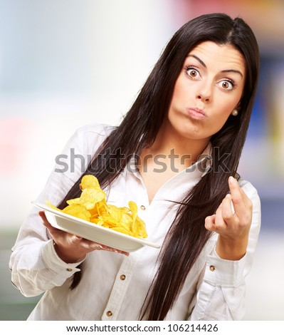 young woman eating potatoe chips against a street background - stock photo