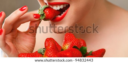 Young woman eating red ripe strawberry close-up studio shot