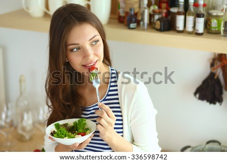 Young woman eating salad and holding a mixed salad  - stock photo