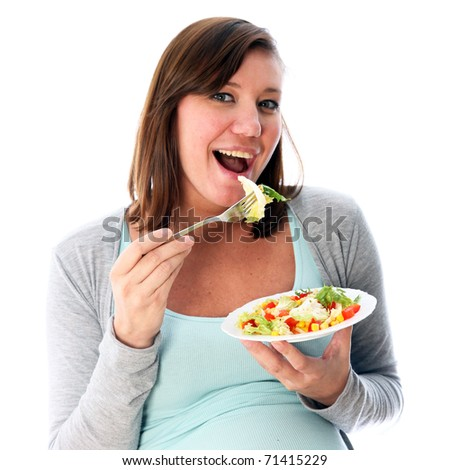 Young woman eating salad delicious and smiles. It carries out the fork to mouth