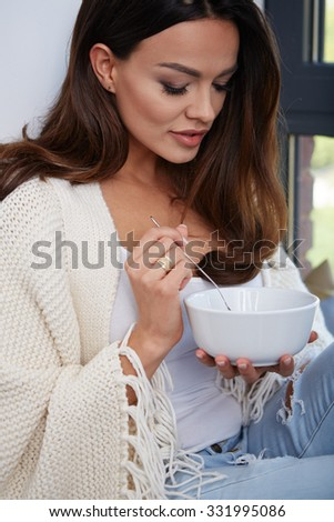 Young woman eating soup by the window.