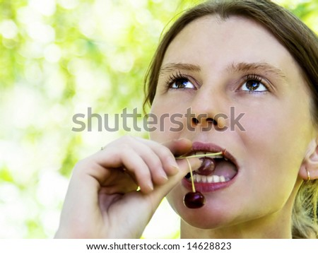 Young woman eating sour cherry - stock photo