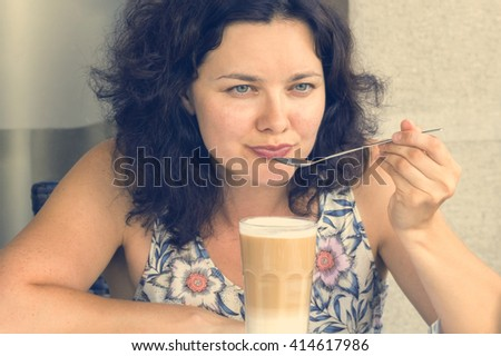 Young woman eating spoon smoothies. Toned