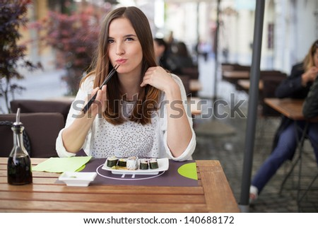Young woman eating sushi in a restaurant - stock photo