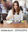 Young woman eating sushi in an Asian restaurant - stock photo