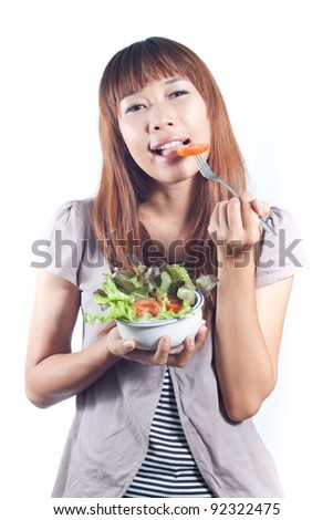 Young woman eating vegetables salad on fork, healthy eating  concept