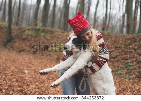 Young woman embrace her cute dog outdoor in the forest - stock photo