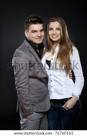 young woman embracing her boyfriend over dark background