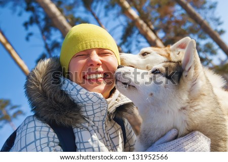 young woman emracing sled dogs - stock photo