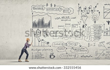 Young woman engineer making effort to move banner with plan sketches - stock photo