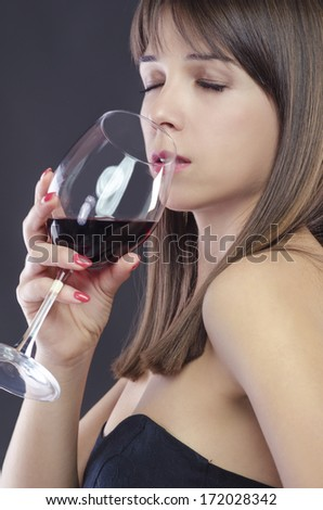 Young woman enjoying a glass of wine - stock photo