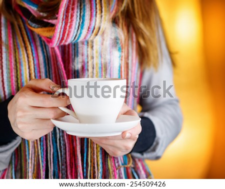 Young woman enjoying a hot coffee in cafe. Woman in fashionable colorful striped scarf. Hipster style. - stock photo