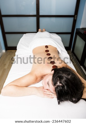 Young woman enjoying a massage in a spa center. - stock photo