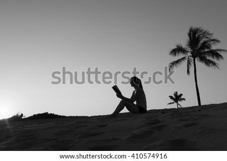 Young woman enjoying a relaxing read on the beach.  - stock photo