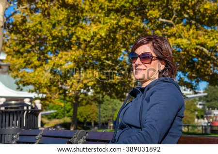 Young Woman Enjoying a Warm Autumn Day in a Park - stock photo