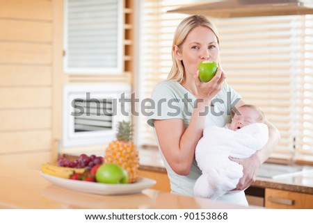 Young woman enjoying an apple with her baby on her arms - stock photo