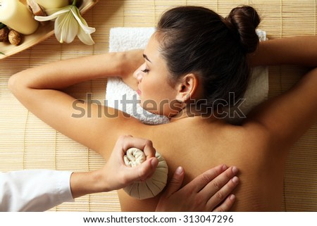 Young woman enjoying back massage in beauty spa salon - stock photo