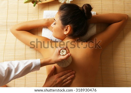 Young woman enjoying back massage in beauty spa salon