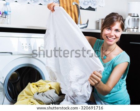 Young woman enjoying clean clothes without stains after laundry - stock photo