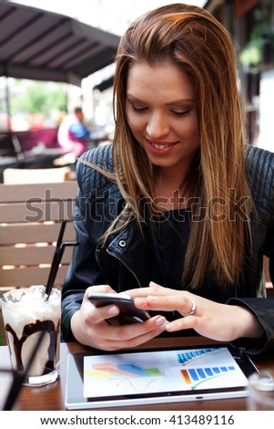 Young woman enjoying coffee at outdoor cafe. Using smart phone.  - stock photo