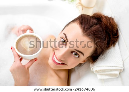 Young woman enjoying coffee while lying in the bath with foam and candles - stock photo