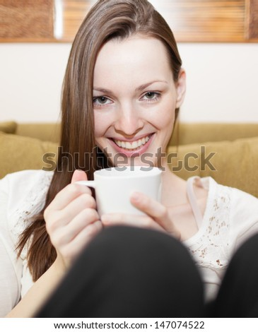 Young woman enjoying cup of coffee - stock photo
