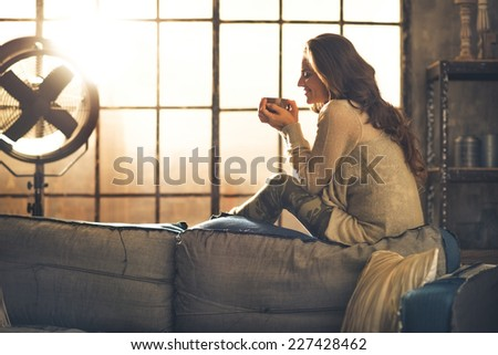 Young woman enjoying cup of hot beverage in loft apartment - stock photo