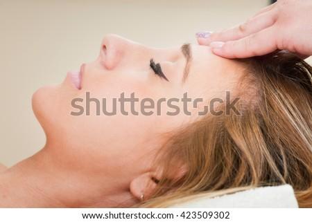 Young woman enjoying facial massage in spa center - stock photo
