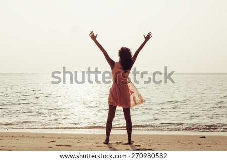 Young woman enjoying freedom feeling happy at beach at sunset. Beautiful serene relaxing girl in pure happiness and elated enjoyment with arms raised outstretched up. Latin Caucasian female model. - stock photo
