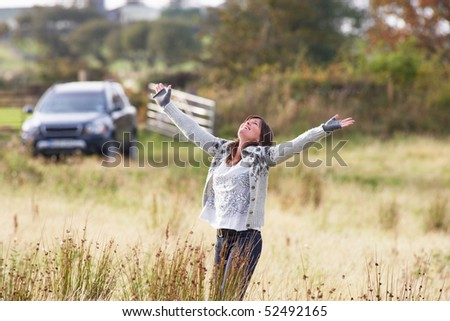 Young Woman Enjoying Freedom Outdoors in Autumn Landscape - stock photo