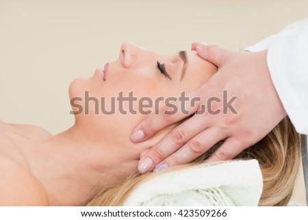 Young woman enjoying head massage in massage center - stock photo