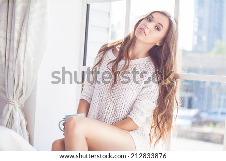 Young woman enjoying her morning coffee. Smiling happy caucasian model in her 20s. - stock photo